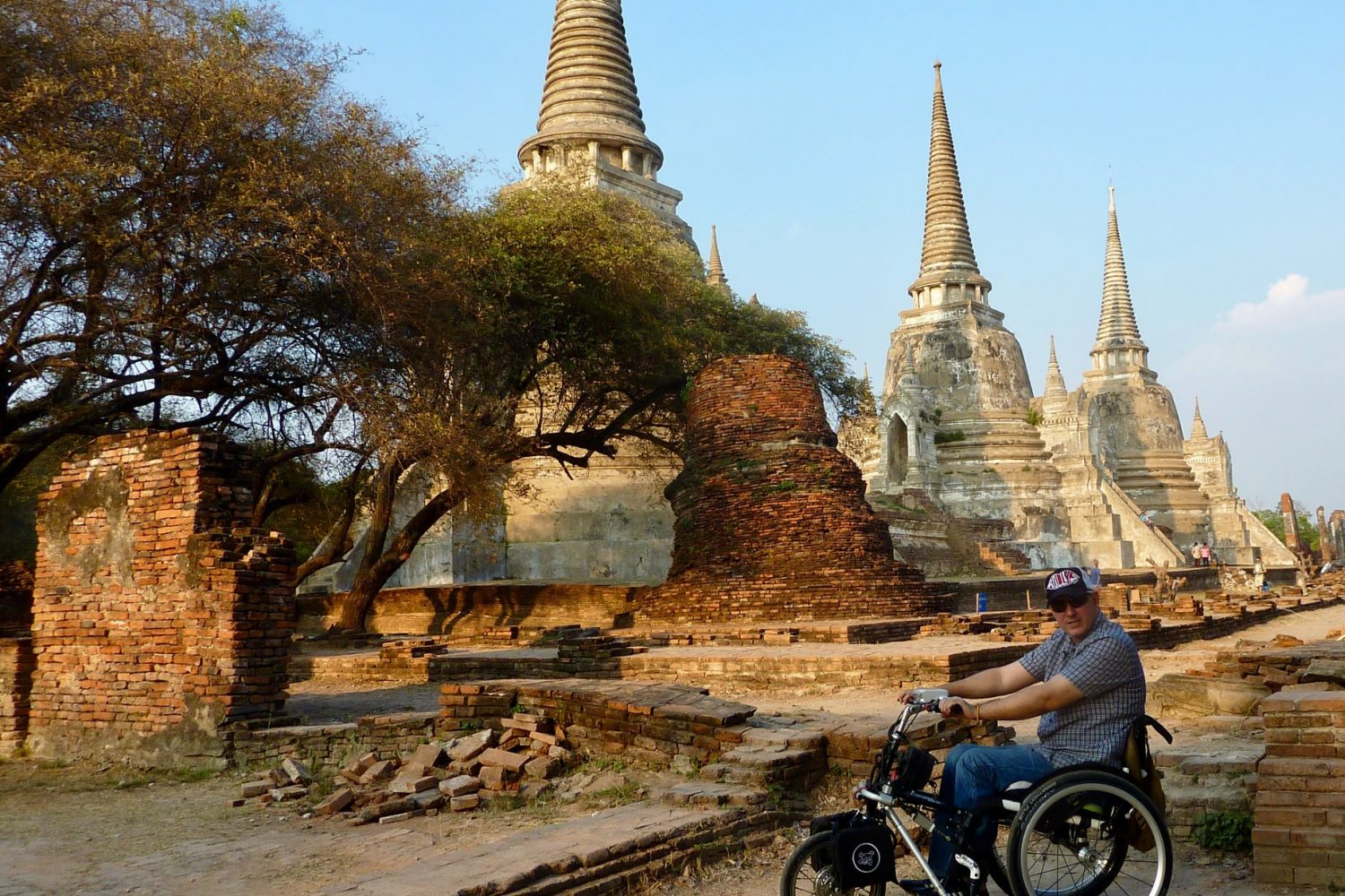 man in a wheelchair with electric triride wheel in front posing in front of conic shaped golden temple buildings