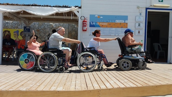 four people in wheelchair doing the little train on the beach pathways and having fun