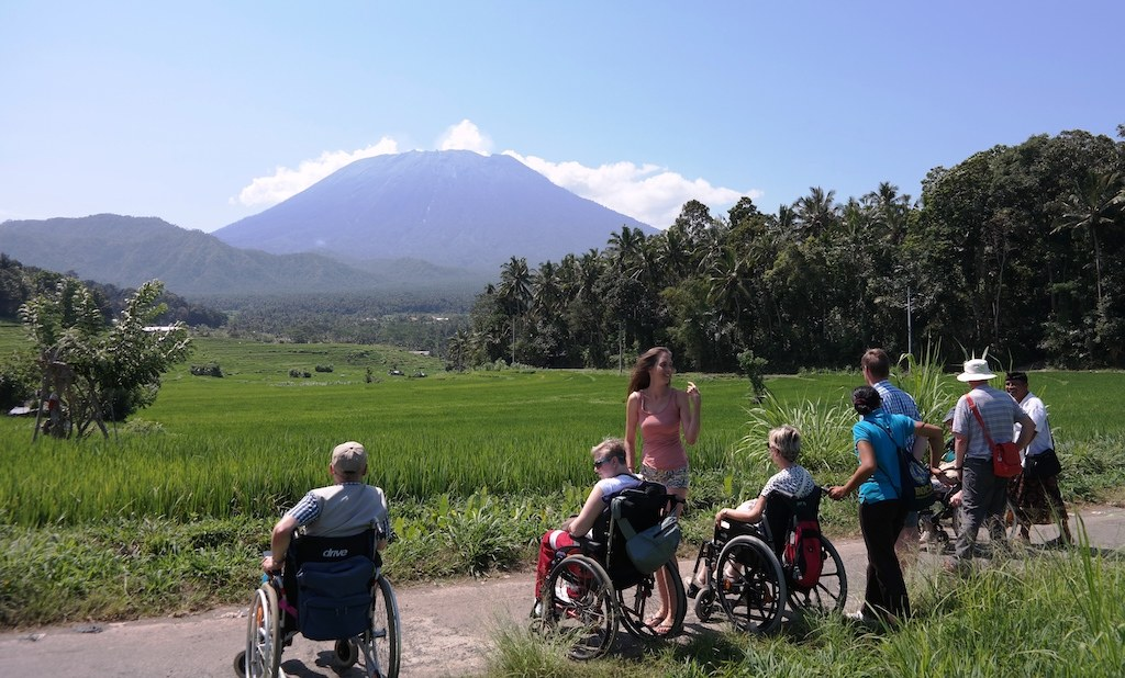 various people in wheelchairs looking at the mount Agung in the distance