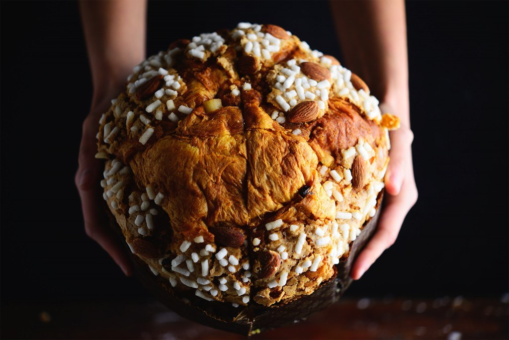 a round bread loaf shaped christmas cake with icing sugar bits on top