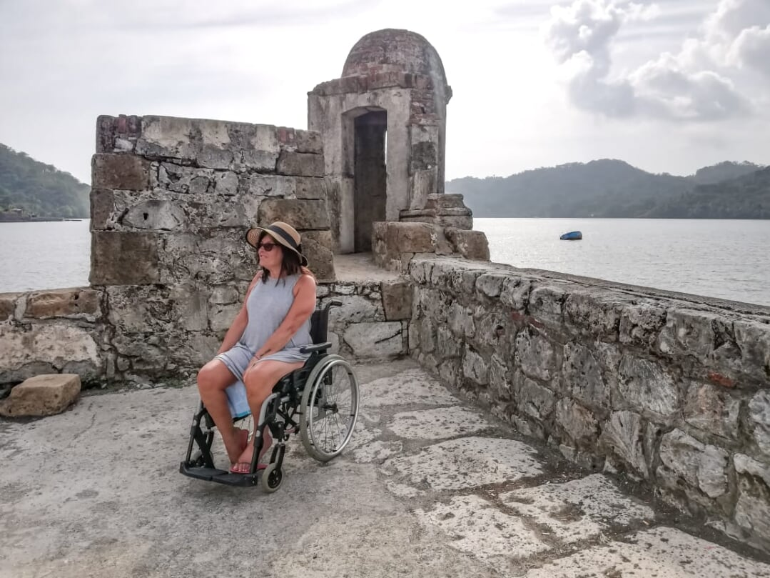 lady in a wheelchair posing near an ancient wall with the sea on the background