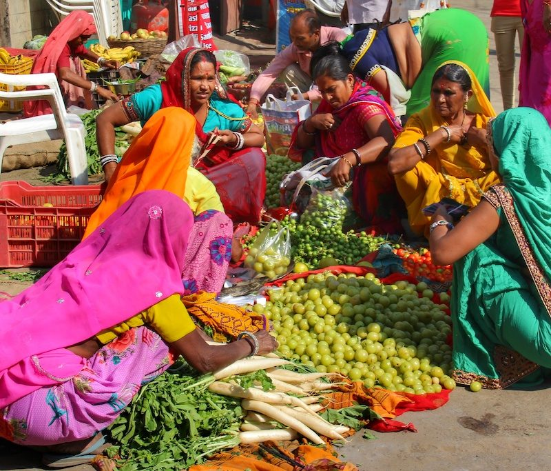 Indian ladies with colourful traditional clothes sitting on the floor at the market