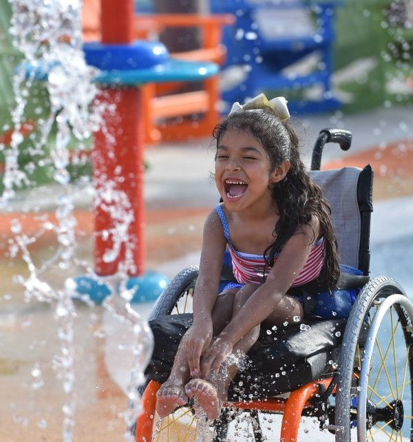 little girl in a wheelchair having fun splashing at the water park