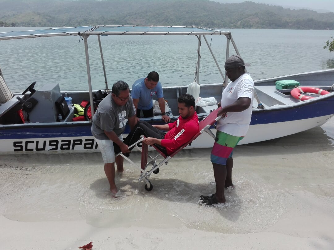 Man in wheelchair being lifted to be on the boat