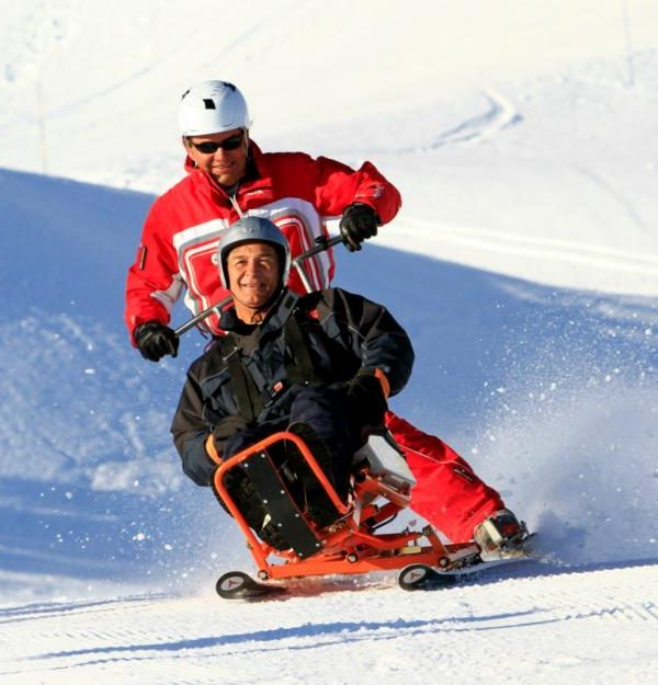a skier with the guide going down the white slopes