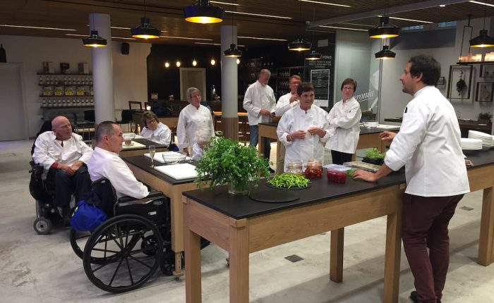 various people standing or on wheelchairs in a fancy kitchen doing a cooking class