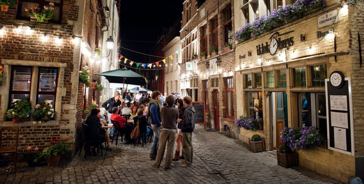 a cobblestone street of ghent all lit up with people having drinks