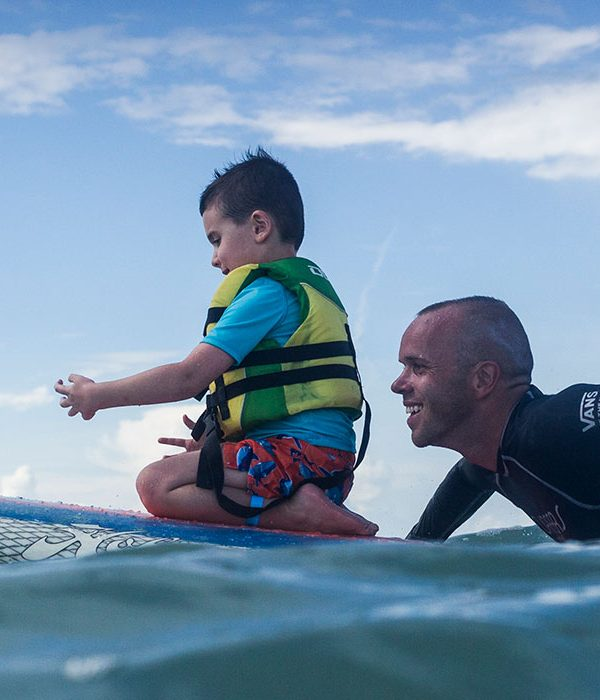 a surfing instructor and a small kid on the surf board in the sea