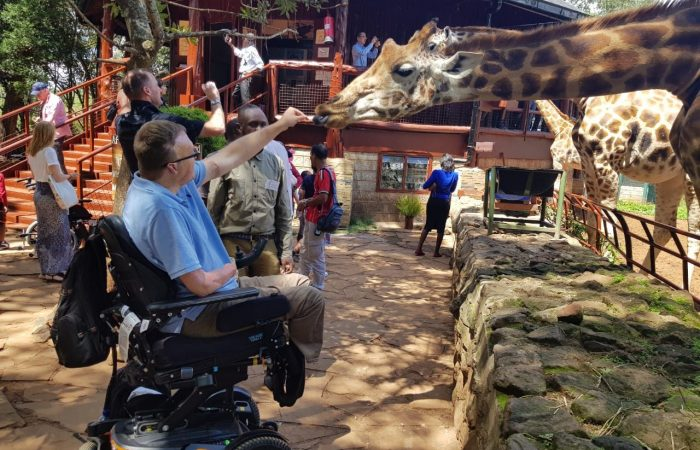 accessible travel blogger john morris feeding a giraffe in Kenya