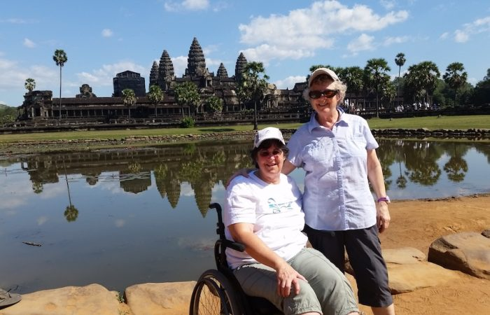 two ladies with big smiles, one standing and one in a wheelchair, with the temples of Angkor Wat in the background
