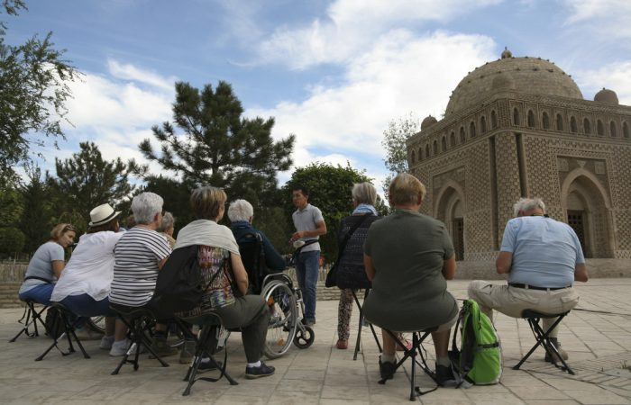 various people in wheelchairs or sitting on stools listening to a guided tour in front of a monument in Boukhara
