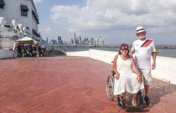 a couple happily posing with the backdrop of ancient and modern Panama city landscape, she is in a wheelchair while he is standing next to her