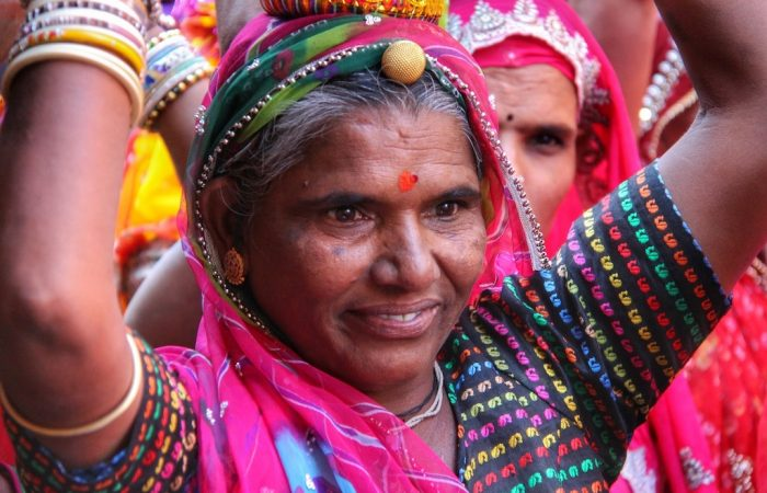a colourfully dressed indian lady carrying a basket on her head smiling