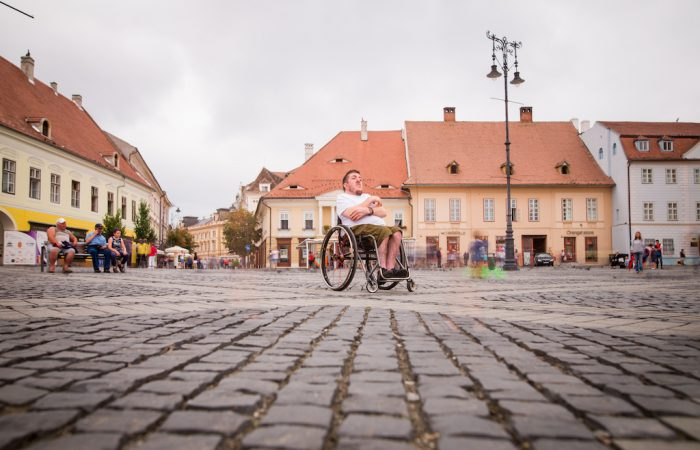 a cobblestone square pavement with a young man on a wheelchair looking around
