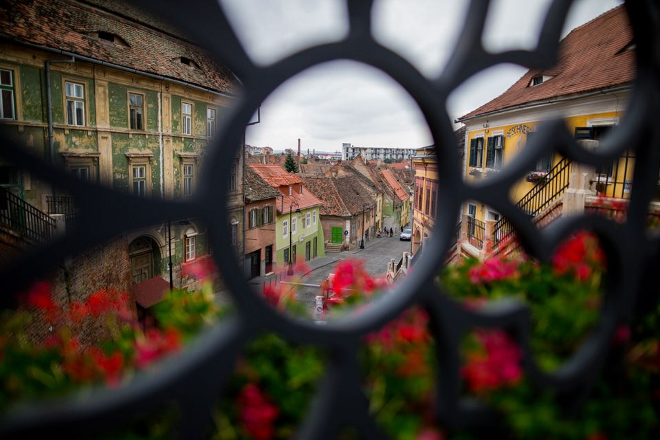 view from a gate of flowered balconies and houses of Sibiu