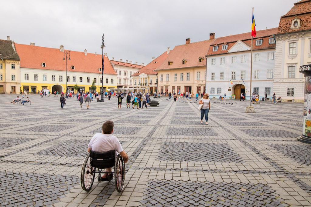 the square of Sibiu with a man in a wheelchair turned around looking at it