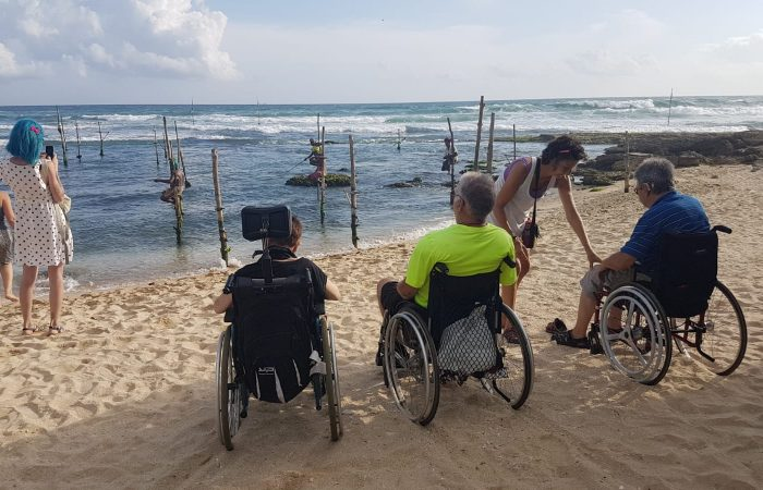 three people in wheelchairs seen from the back at the beach