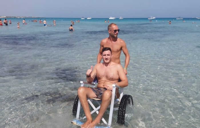 two gentleman of which one in a beach wheelchair enjoying a bath in the cristalline sea
