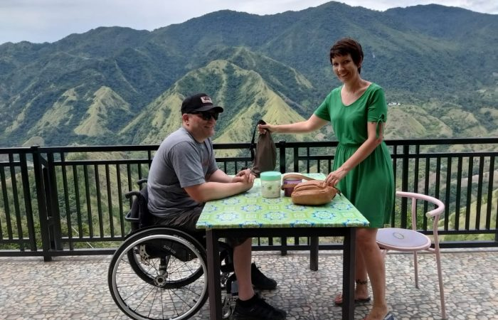 a couple at a table in a terrace with a mountain green background, the gentleman is on a wheelchair and the lady is standing up