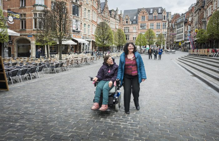 two ladies strolling through the cobblestoned streets of Leuven, one using an electric scooter