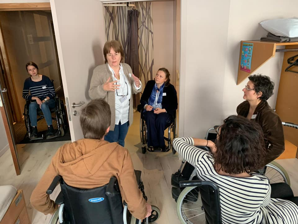 Anne of decalage association explaining accessible hotels to 4 people in a training who are sitting in wheelchairs