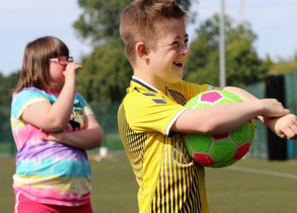 two children with down syndrome while playing rugby