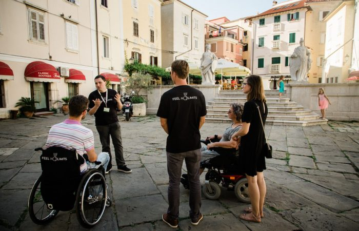 two travelers in wheelchairs and their guide in the streets of Piran