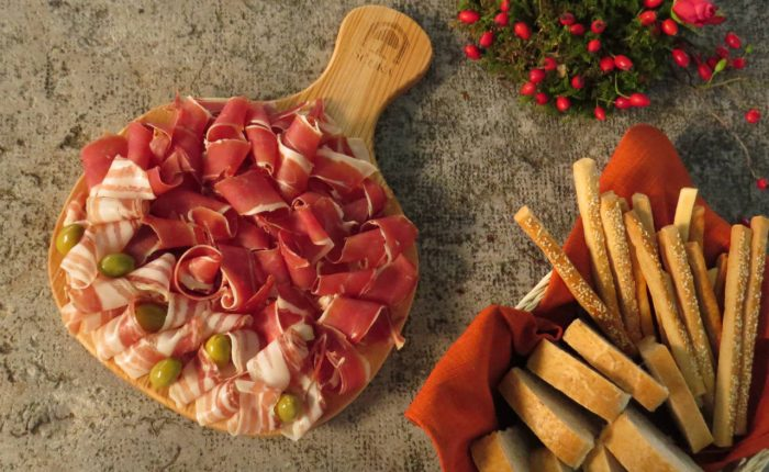 a big dish of various hams from slovenia and some grissini
