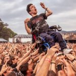 young guy in a wheelchair at a rock concert being carried on top of the crowd