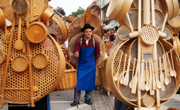a wood carving artisan standing in front of his many creations