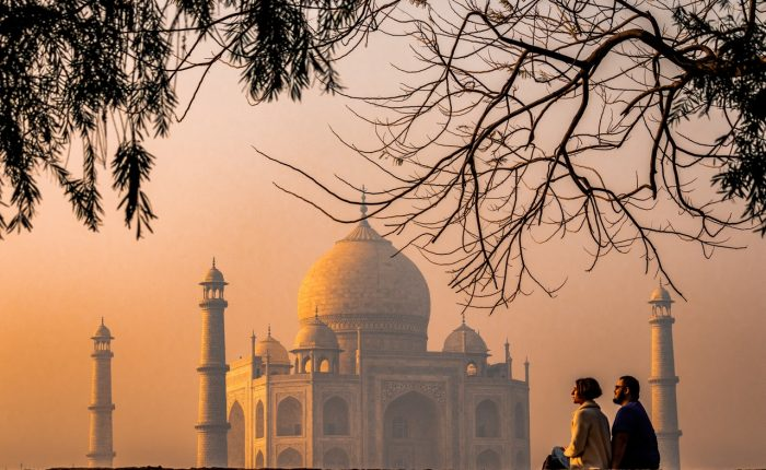 view of the Taj Mahal at dawn with a couple sitting looking towards it