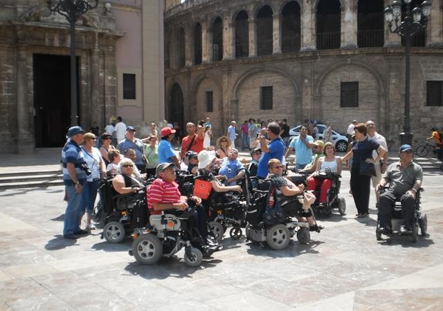 a group of 7 wheelchair users of various ages and sexes with their walking friends and their guide in a square in Valencia