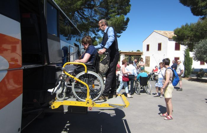 A lady in a wheelchair on a lift about to get into a coach, there are other people around and she has a gentleman behind her holding her chair