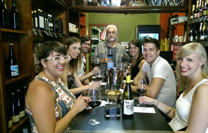 6 people of various ages and sex with the sommelier Johan doing a wine tasting in a cantina