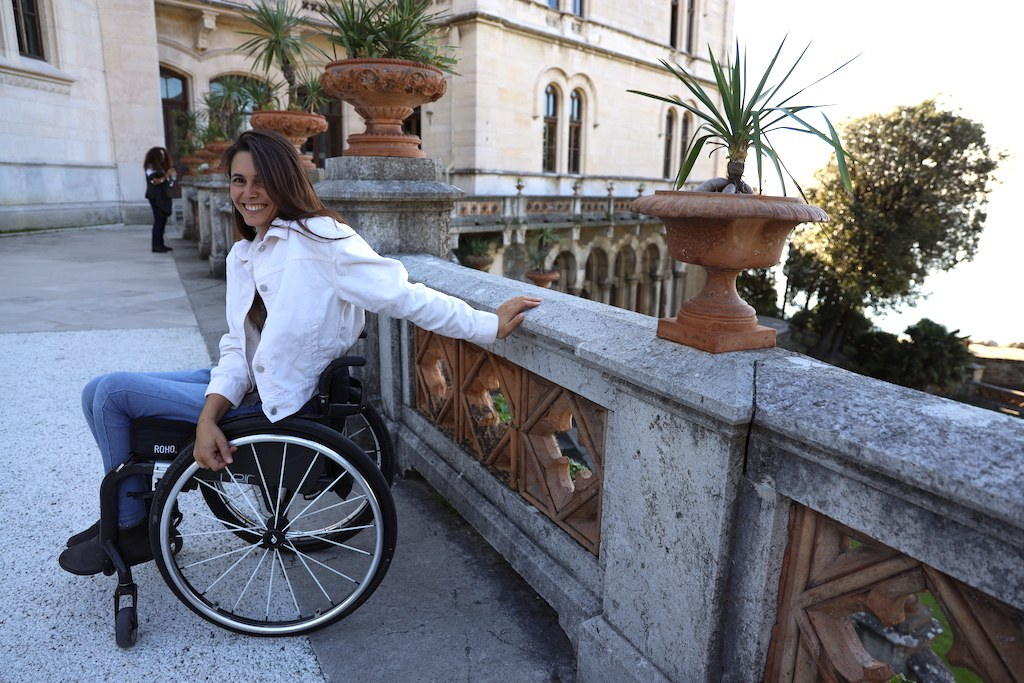 Giulia on her wheelchair and leaning on the marble parapet of the gardens of the Miramare Castle