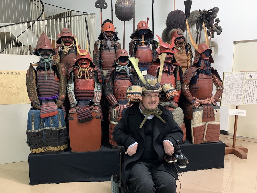 Josh who is in a museum on Tottori Island. He is posing in front of some traditional samurai clothes. He is from the front, wearing a samurai hat on his head and smiling.