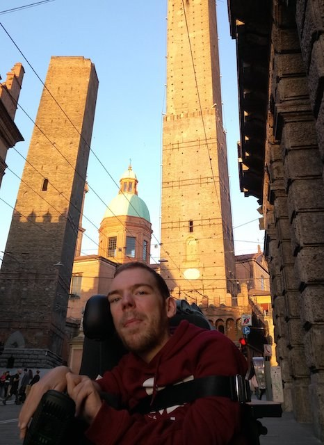 Photo of Kamil posing in front of the Bologna tower at sunset. He is wearing a red sweater and looking at the camera.
