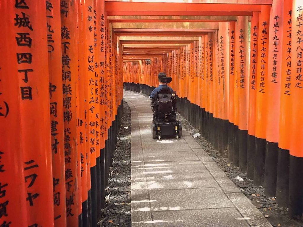Josh is from behind in his wheelchair wearing a black t-shirt. He is exploring fushimi inari taisha in kyoto. There are a lot of traditional wood architecture paint in red all around him with Japanese writings and they are forming a path.