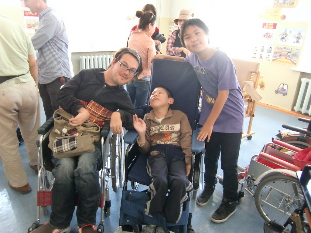 Photo of Josh in Mongolia in what appears to be a school. He is next to two children, one in a wheelchair in the middle. They are smiling at the camera. The weather is nice. Josh is on the left wearing a black top and blue jeans. The boy in the wheelchair in the middle is wearing a brown sweater and black training pants and the boy on the right is wearing a purple t-shirt with black pants. There are three women in the background and two men.