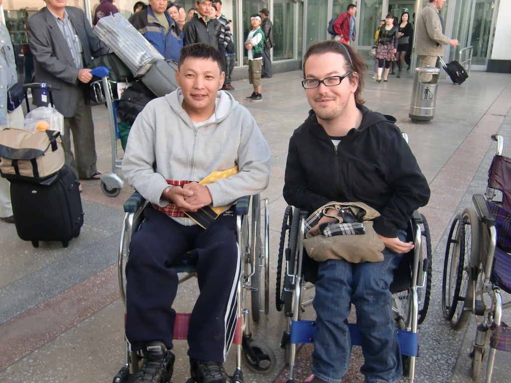 Photo of Josh in Mongolia. He is outside in what appears to be a bus station or airport. He is posing to the right of a man who may have benefited from a wheelchair. They are both smiling at the camera. Josh is wearing a black jacket and jeans. The man to his left is wearing a gray jacket and dark blue training.