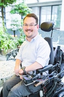 portrait of josh grisdale smilin on his wheelchair and wearing a pale blue shirt with rolled up sleeves