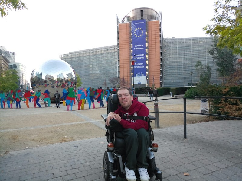 Photo of Kamil in front of the European Commission in Brussels. He smiles at the camera. He is wearing a red sweater and black pants. Behind him there is also an open air exhibition of people holding hands around a large metal ball.