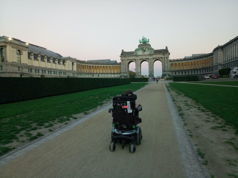 Photo by Kamil at the Parc du Cinquantenaire in Brussels.  It's late afternoon and it's a bit dark. Kamil is from the back on a dirt road and walks towards the arch of the Cinquantenaire.