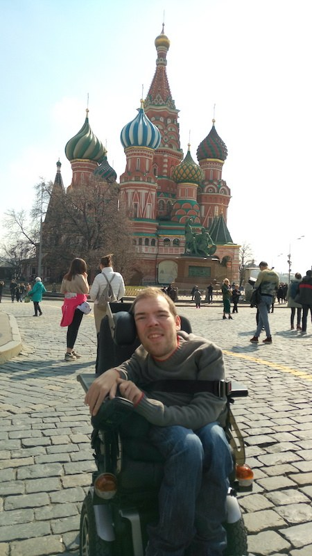 Photo of Kamil on Red Square in front of Basil the Blessed Cathedral in Moscow, Russia. It is sunny. Kamil is facing the camera and smiling. He is wearing a green sweater and jeans.