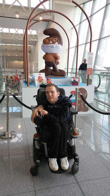 Photo of Kamil in an airport in Belgium. He is posing in front of a statue of the chief of the Smurfs made of chocolate. He is wearing a dark blue sweater and black pants with white sneakers.
